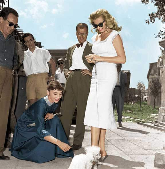 Hepburn takes a break on the set of War and Peace with Swedish actress Anita Ekberg and producer Dino De Laurentiis (far left), 1955