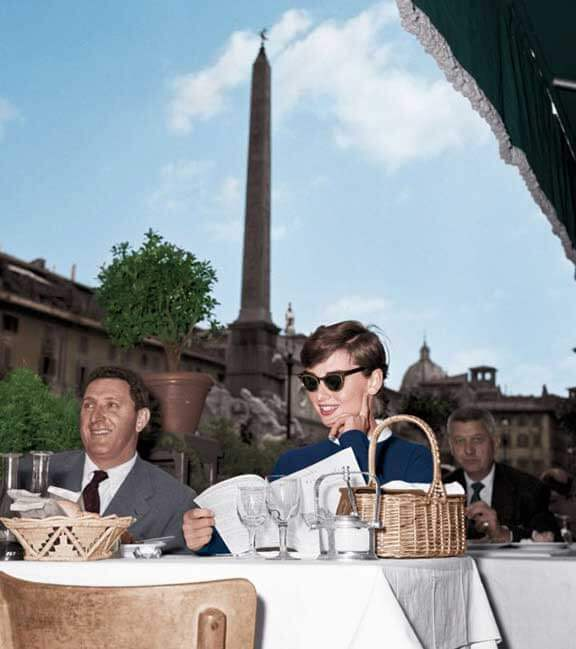At a café in the Piazza Navona with her signature basket purse, 1955